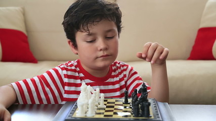 Little boy learning how to play chess