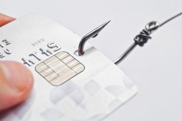hand holding a credit card with a fish hook