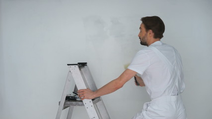 handsome male painter paiting the wall