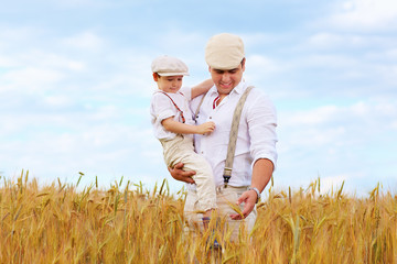 father and son, farmers on wheat field