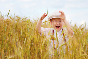 happy boy running on wheat field