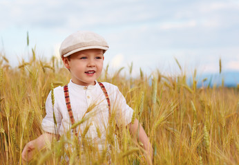 happy boy walking the wheat field