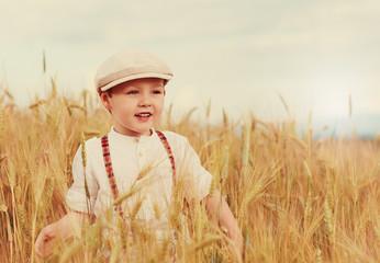 happy boy walking the wheat field