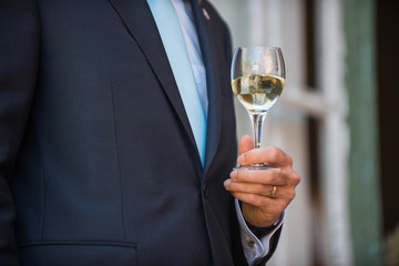 man holding a glass of white wine