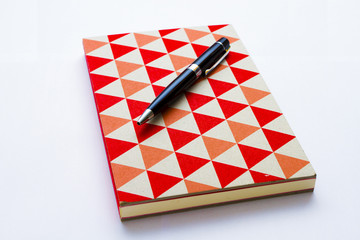 Colorful notebook and pen isolated on the white