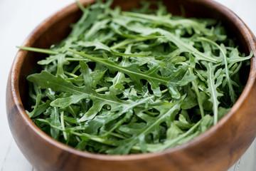 Fresh arugula lettuce in a wooden bowl, close-up, studio shot