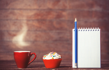 Cup of coffee with cupcake and notebook on wooden background.
