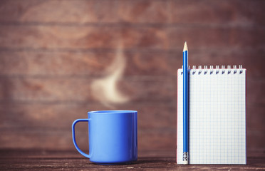 Cup of coffee and notebook on wooden background.