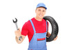 Male mechanic holding a wrench and a tire