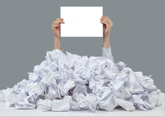 Hands reaches out from big heap of crumpled papers
