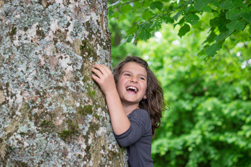 Happy laughing Girl holding big tree