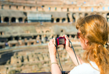 Young female tourist takes a picture inside the Coliseum in Rome