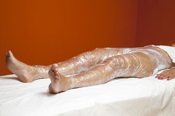 Female body being wrapped around with foil to reduce fat