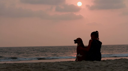 woman hugs her dog at sunset