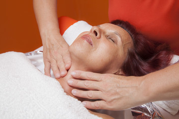Cute woman gets professional facial massage, lymphatic drainage