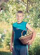 teenager with a basket of apples in a garden,with a retro effect