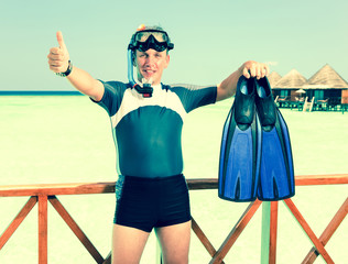 Young sports man with flippers,mask and tube near the ocean.