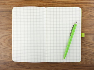 Open blank checked notebook with green pen on a table.