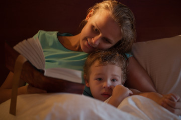 Mother reading a bedtime story to her little son