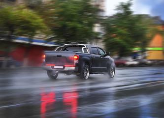 pickup goes on the rainy city street