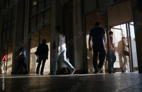 Shoppers entering and leaving a store - 65753499
