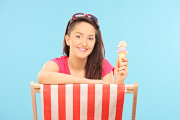 Woman eating ice cream seated on sun lounger