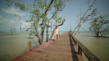 Woman walking on wooden pier