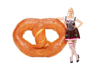 German girl standing by a huge pretzel