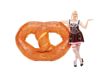 Bavarian girl leaning on an enormous pretzel