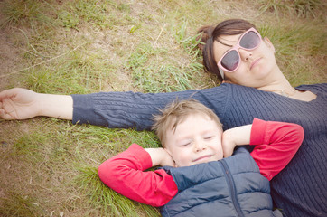 Mother and her young son lying on the ground