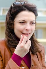 Beautiful young woman applying lipstick