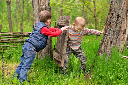 Two young boys fighting over a rustic old gate