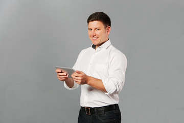 smiling young male executive using digital tablet against gray