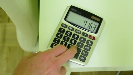 calculator on the table - man counts on a calculator