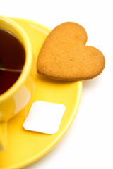 yellow cup with tea bag and heart-shaped cookie