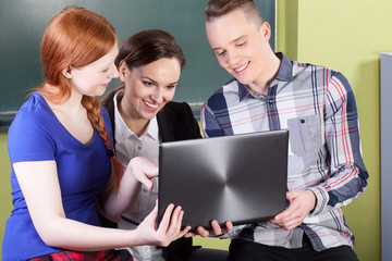 Teacher and students using laptop