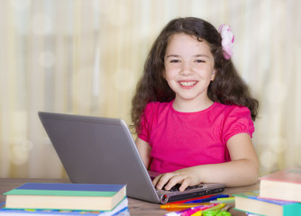 Smiling school girl with laptop at desk