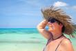 Frau mit Sonnenhut und Sonnenbrille am Strand