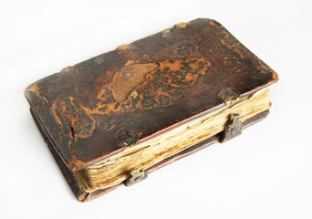 Ancient worn book with leather cover on light background
