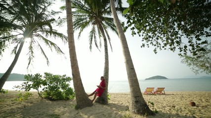 Woman using digital tablet by the beach