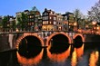 Canal houses of Amsterdam with bridge lit at night, Netherlands