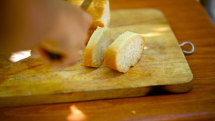Baker Slicing french Bread on a Cutting Board