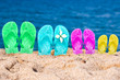 Flip flops of a family of four in the sand of a beach - 65765825