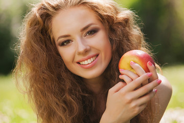portrait pretty smiling woman holding apple. background summer