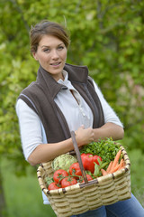 Beautiful woman holding basket of vegetables