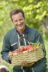 Farmer in garden holding basket of fresh vegetables