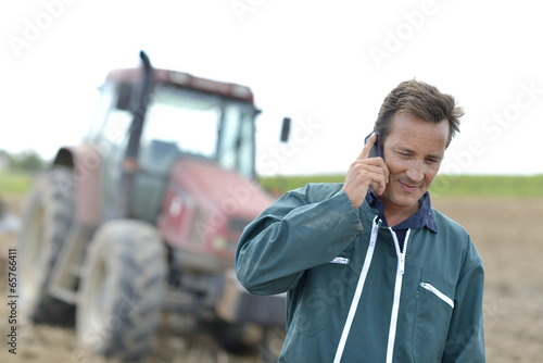 Farmer walking in field and talking on mobile phone - 65766411