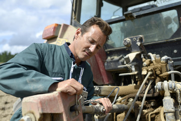 Farmer working on tractor in farming land