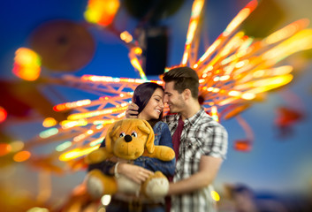 Love couple with colorful carousel in background