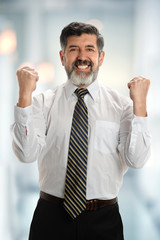 Hispanic Businessman Celebrating in Office